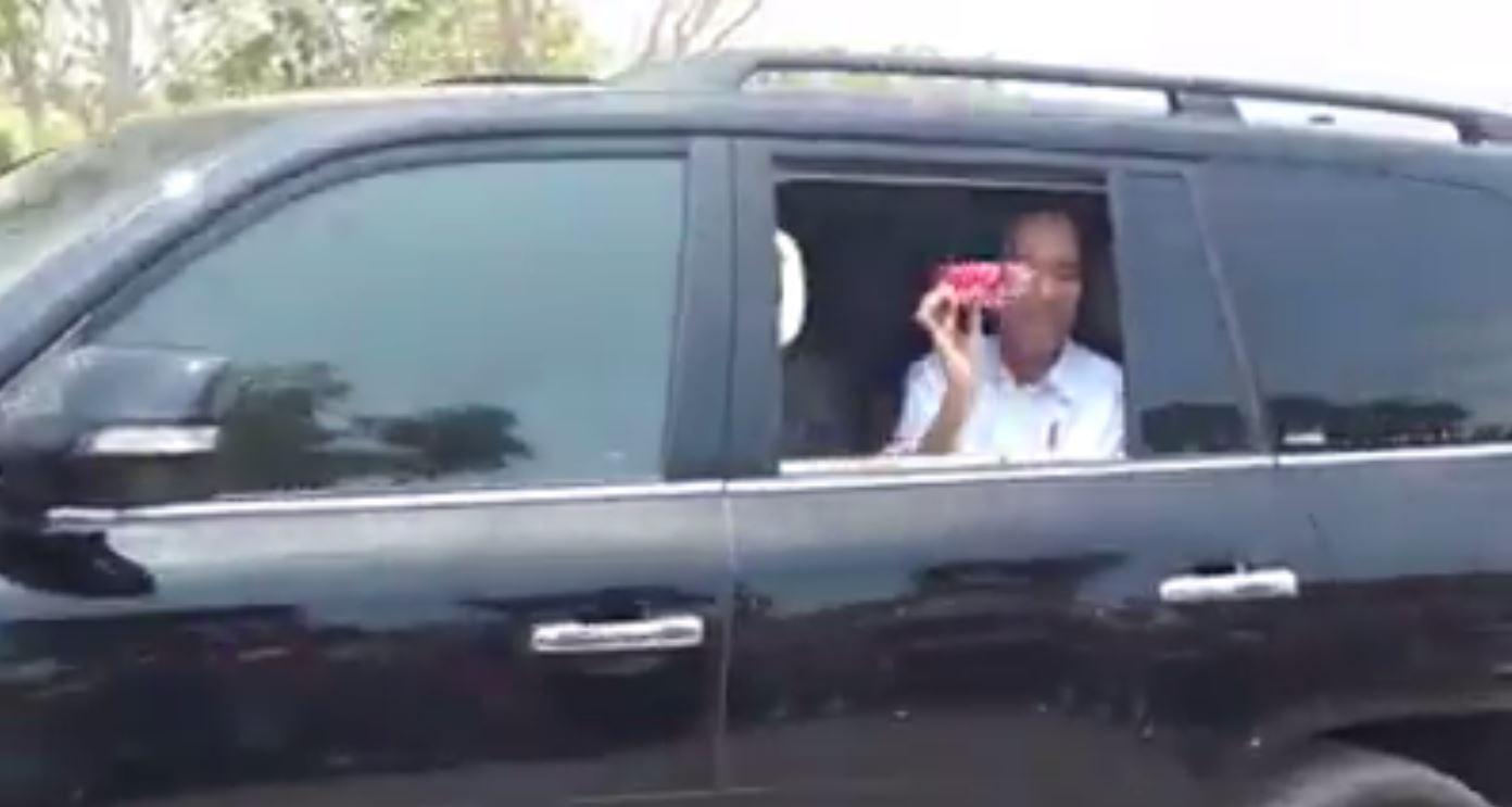 Presiden Jokowi melempar hadiah dari dalam mobil (IST)