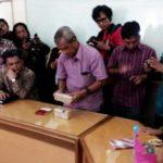 Istri terduga teroris Sriyono yang tewas setelah berduel dengan anggota Densus, menyerahkan barang bukti dua bungkus uang ke Kantor PP Muhammadiyah, Yogyakarta (Dok.Liputan6)